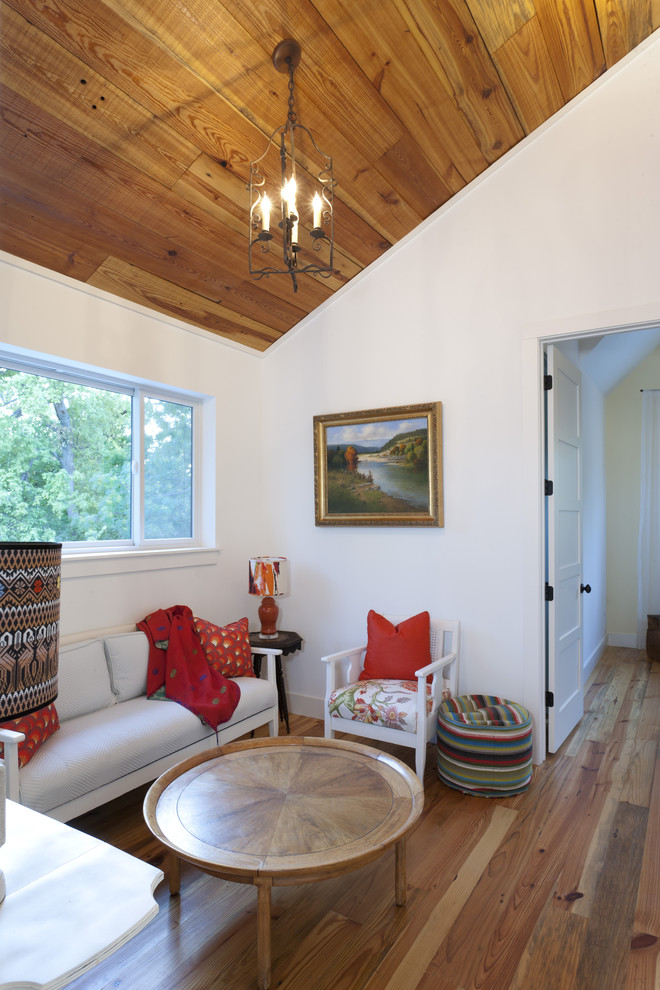 Inspiration for a country medium tone wood floor family room remodel in Austin with white walls