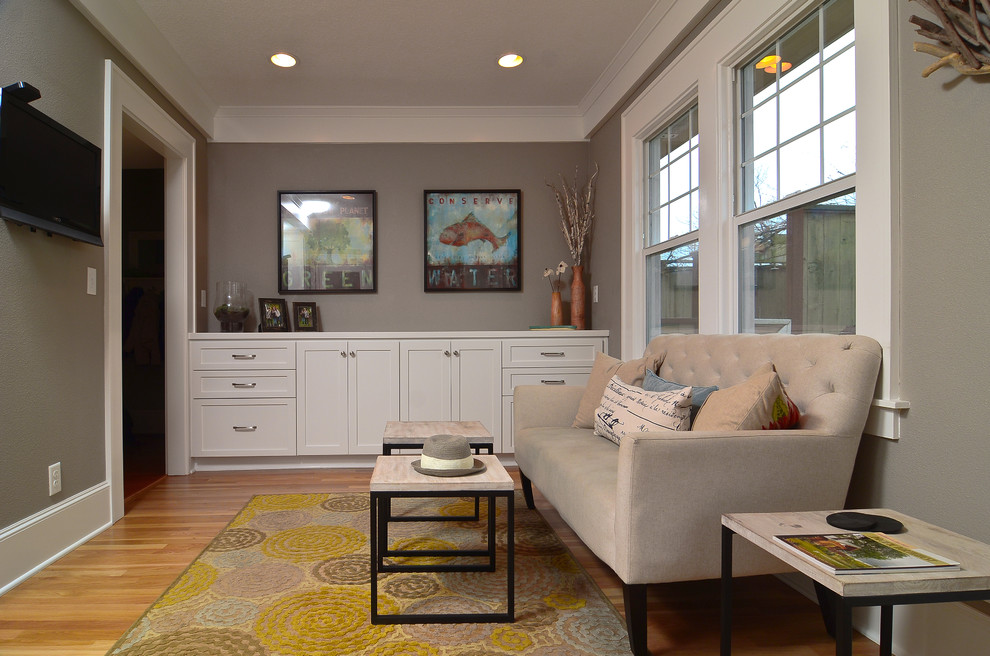 Trendy enclosed medium tone wood floor family room photo in Portland with gray walls and a wall-mounted tv