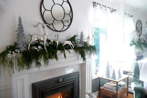an elegant mantel with silver figurines and a lush garland