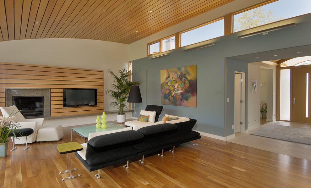 Inspiration for a contemporary family room remodel in San Francisco with a wood fireplace surround