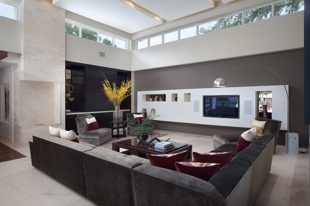 Trendy open concept beige floor family room photo in Orlando with gray walls and a media wall