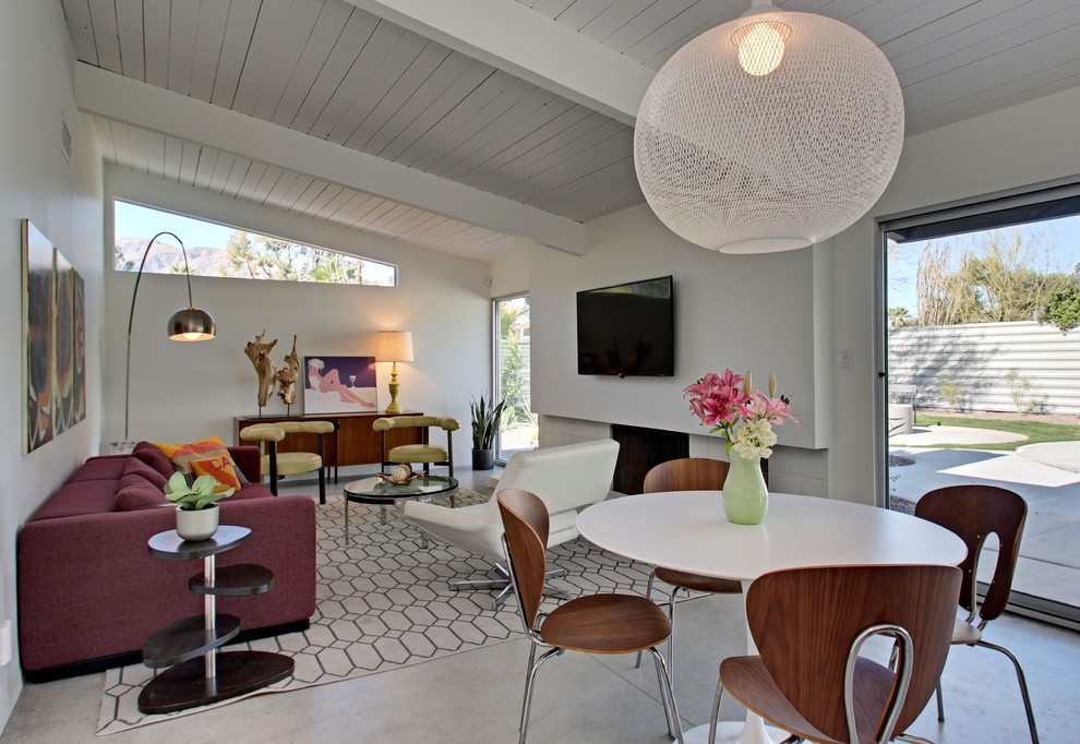 Example of a mid-sized mid-century modern open concept concrete floor family room design in Los Angeles with white walls, a standard fireplace, a tile fireplace and a wall-mounted tv