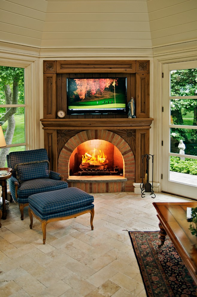 Elegant family room photo in Chicago with beige walls, a standard fireplace, a brick fireplace and a wall-mounted tv