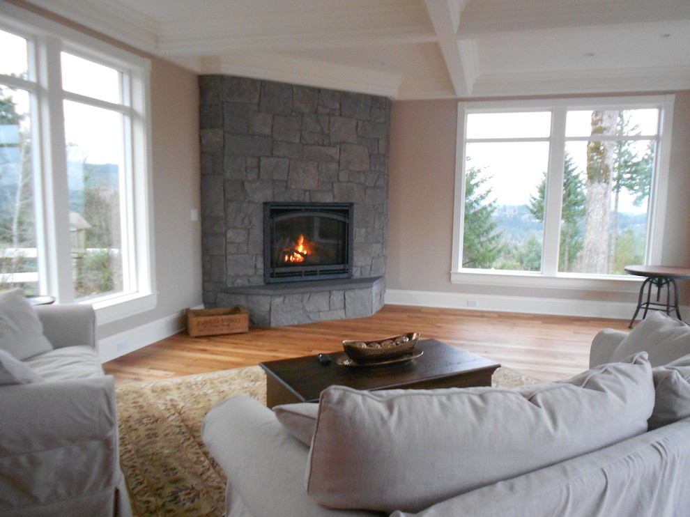 Example of a large classic enclosed medium tone wood floor game room design in Portland with beige walls, a corner fireplace and a stone fireplace