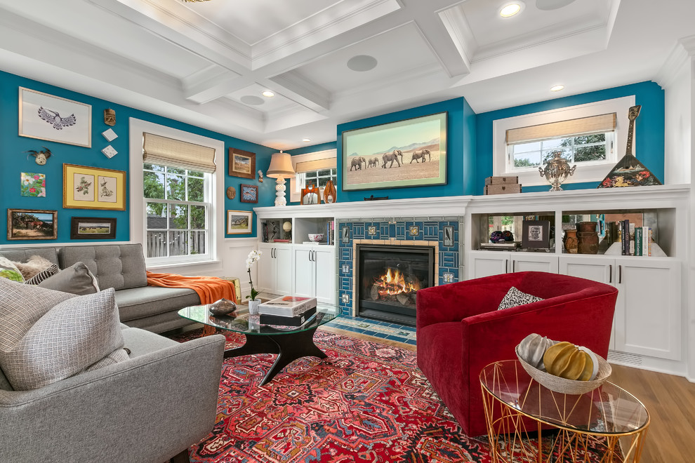 Mid-sized eclectic medium tone wood floor family room library photo in Minneapolis with blue walls, a standard fireplace, a tile fireplace and a wall-mounted tv
