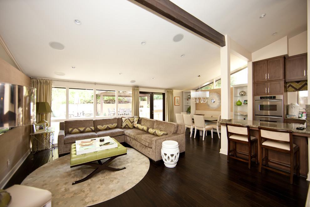 Example of a trendy open concept dark wood floor and brown floor family room design in Los Angeles with beige walls