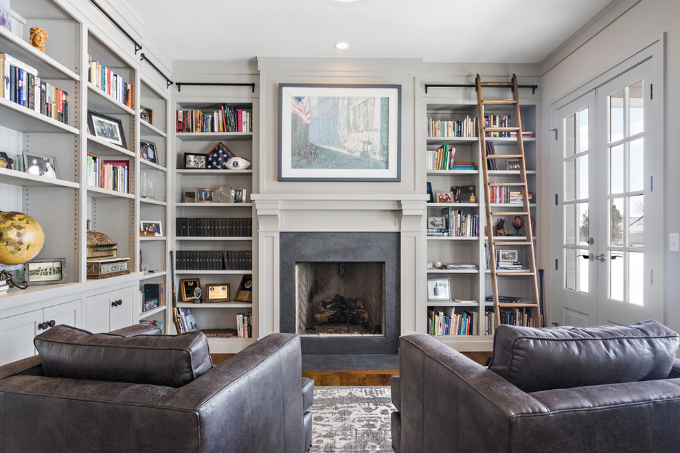 Example of a classic enclosed dark wood floor family room library design in Other with gray walls, a standard fireplace and no tv
