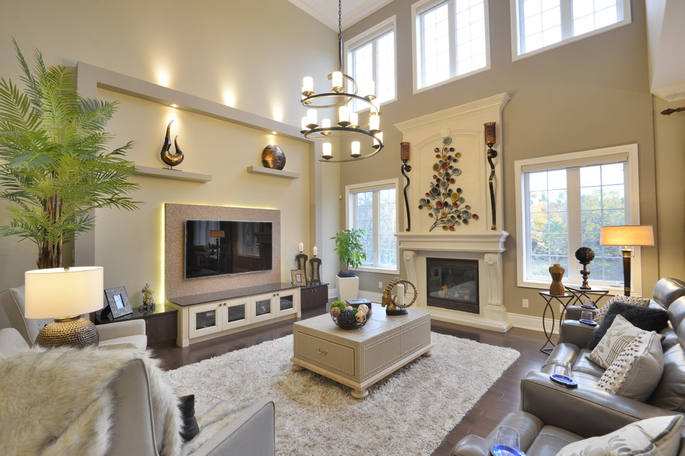 Inspiration for a mid-sized transitional open concept dark wood floor and beige floor family room remodel in Toronto with beige walls, a standard fireplace, a wall-mounted tv and a wood fireplace surround