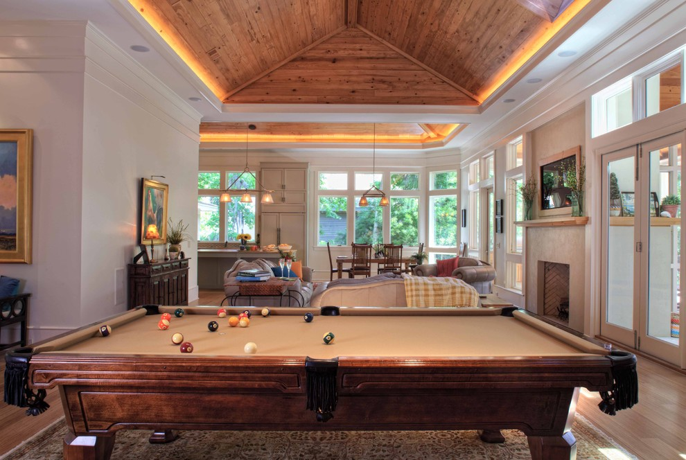 Example of a trendy light wood floor game room design in Atlanta with a standard fireplace, a concrete fireplace and a concealed tv