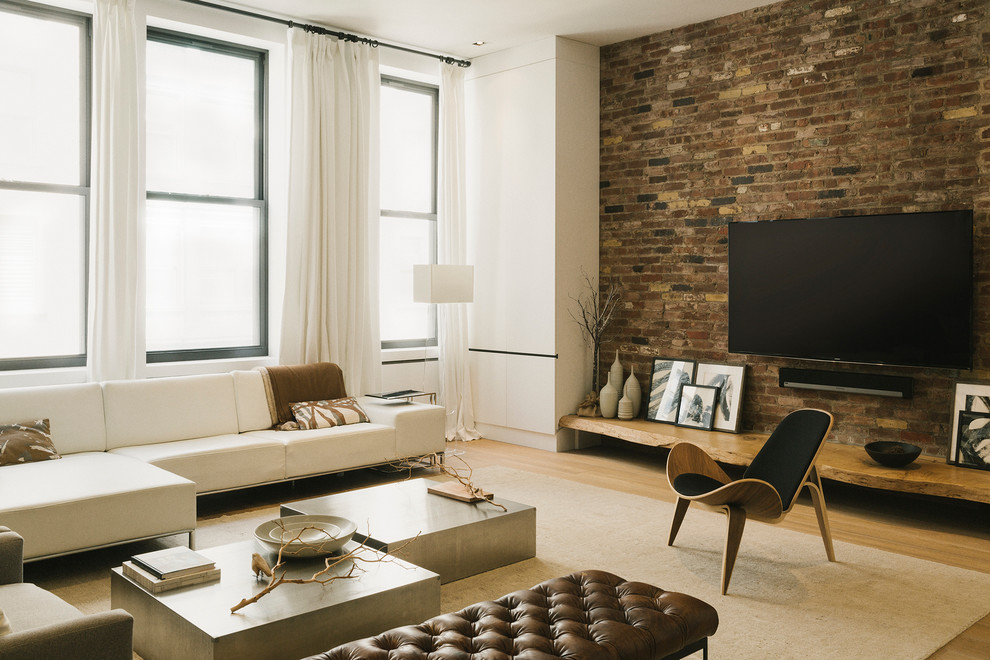 Large urban open concept light wood floor and beige floor family room photo in New York with white walls, a wall-mounted tv and no fireplace