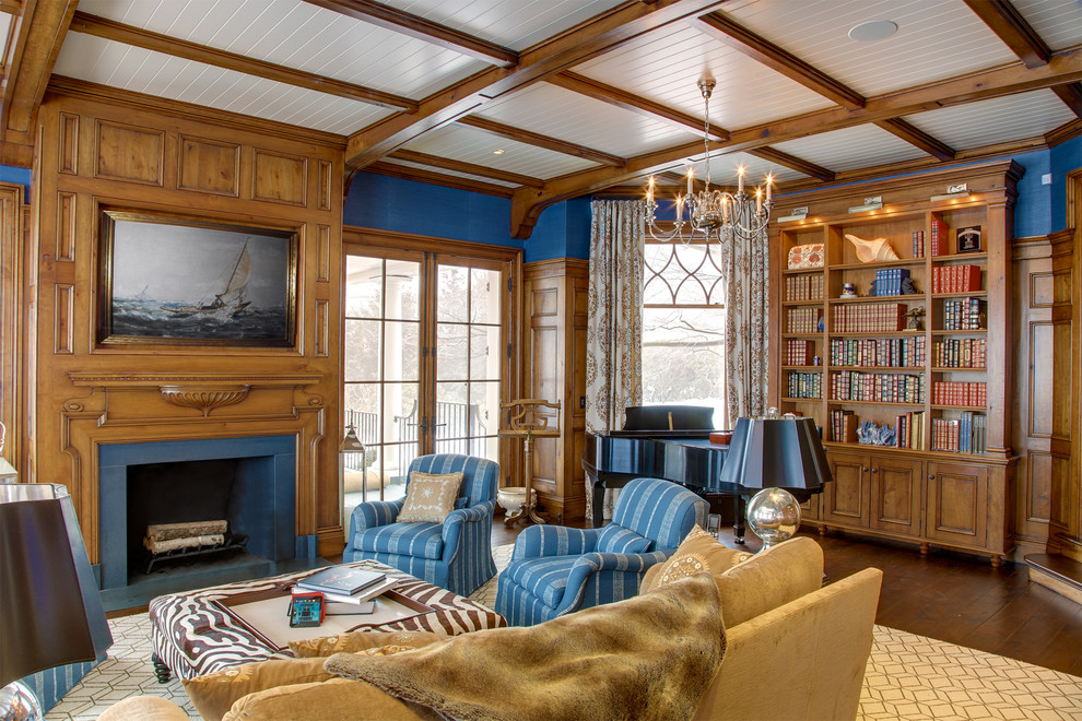 Large elegant enclosed medium tone wood floor and brown floor family room library photo in Other with blue walls, a standard fireplace, no tv and a wood fireplace surround