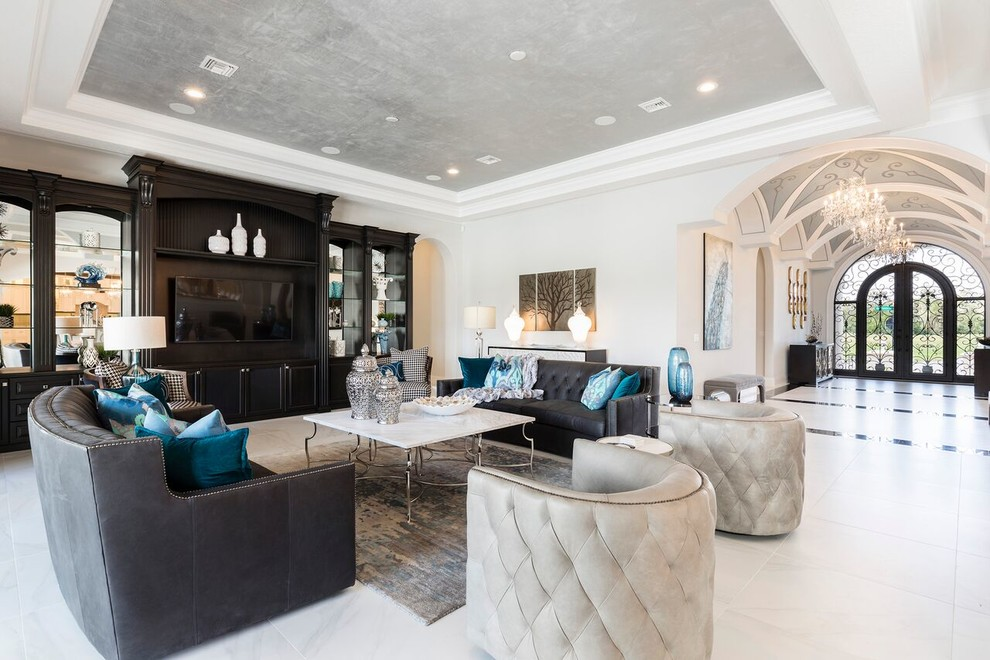 Family room - mediterranean open concept gray floor family room idea in Orlando with gray walls and a media wall