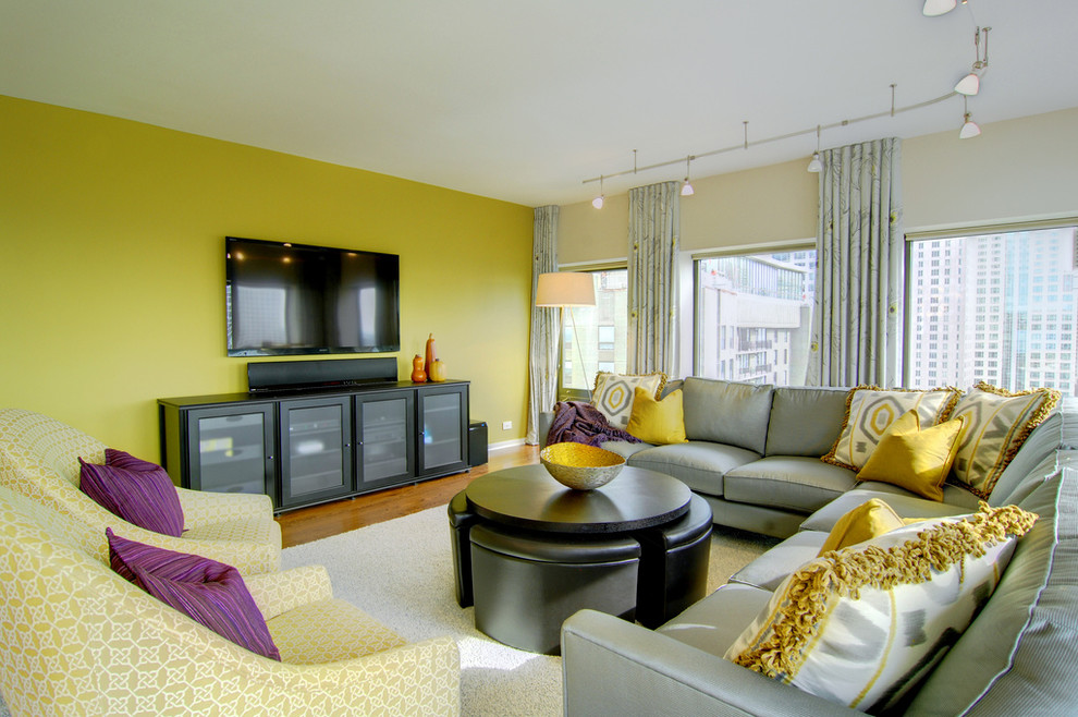 Example of a large trendy open concept light wood floor family room design in Phoenix with yellow walls, no fireplace and a wall-mounted tv
