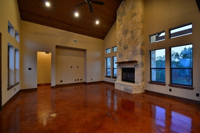 Mid-sized trendy open concept concrete floor family room photo in Austin with a standard fireplace, a stone fireplace, beige walls and no tv