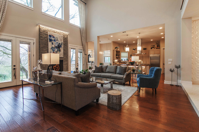 Inspiration for a large contemporary open concept medium tone wood floor and brown floor family room remodel in Dallas with gray walls, a standard fireplace and a stone fireplace