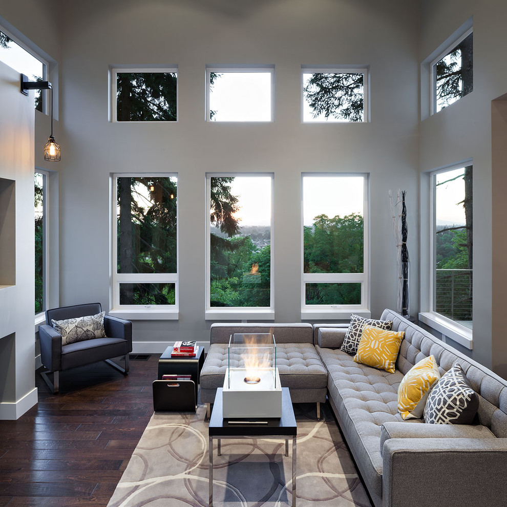 Large trendy open concept dark wood floor family room photo in Portland with gray walls and a ribbon fireplace