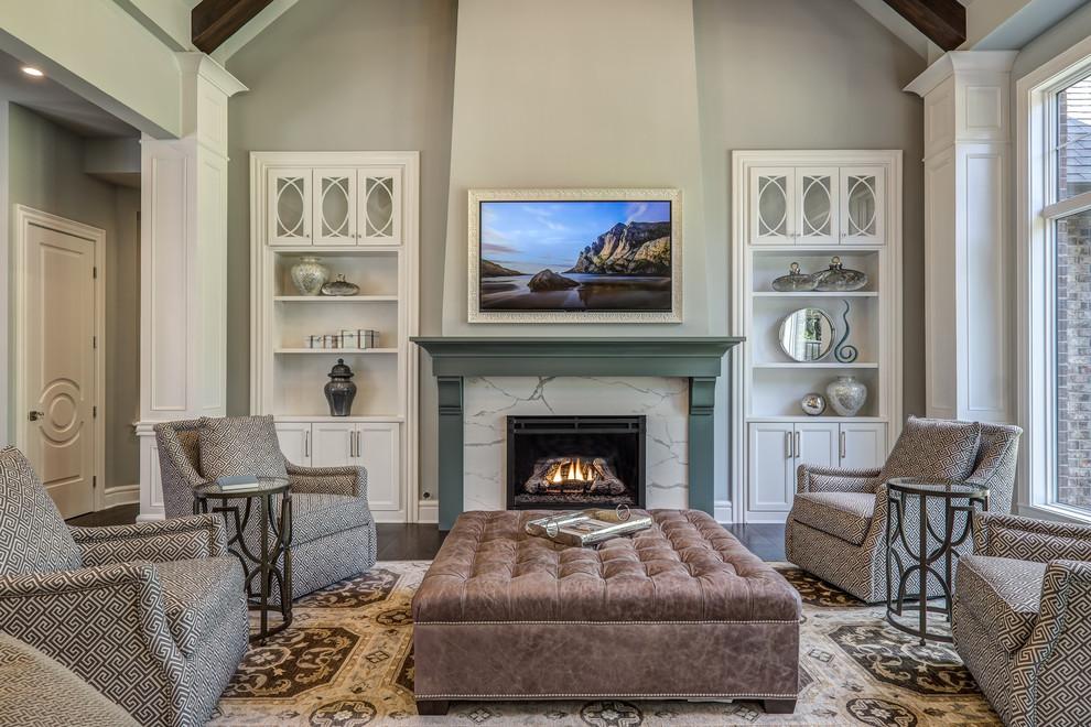 Imagen de sala de estar abierta, tradicional, grande, con paredes grises, todas las chimeneas, marco de chimenea de piedra, televisor colgado en la pared, suelo de madera oscura y suelo marrón