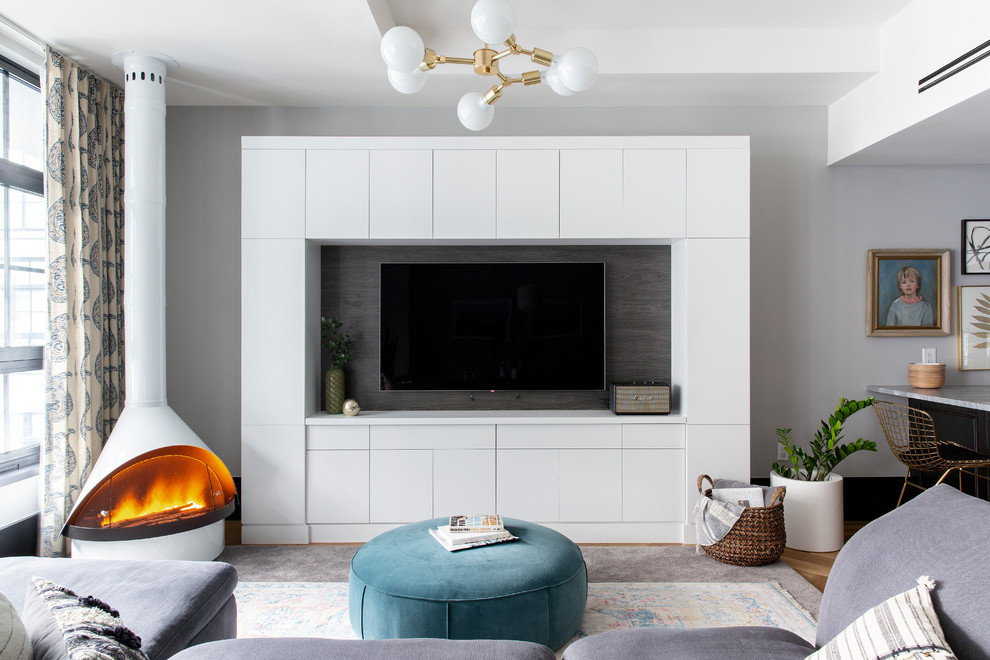 Example of an eclectic open concept family room design in New York with gray walls, a wood stove and a media wall
