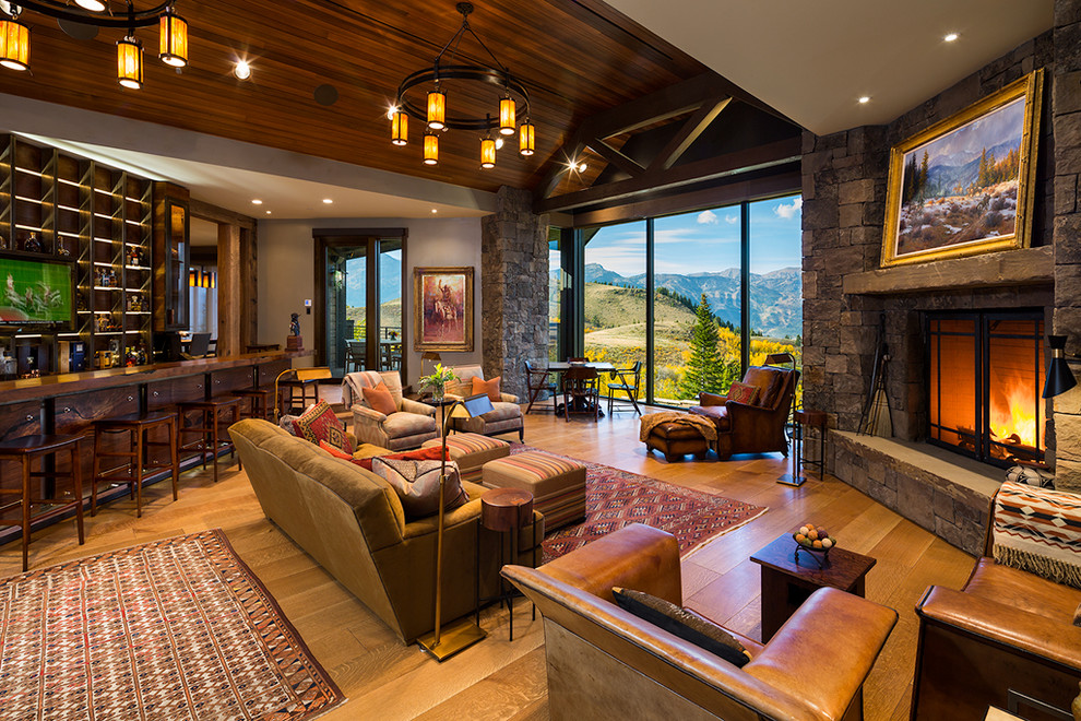 Inspiration for a large rustic open concept medium tone wood floor and brown floor family room remodel in Other with a stone fireplace, a standard fireplace, beige walls and no tv