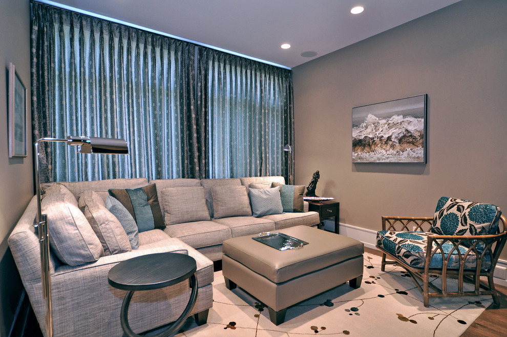 Example of a transitional medium tone wood floor family room design in Calgary with beige walls