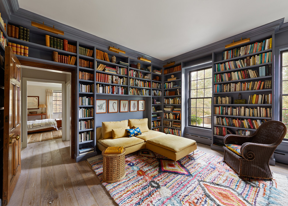 Inspiration for an eclectic medium tone wood floor and brown floor family room library remodel in New York with purple walls