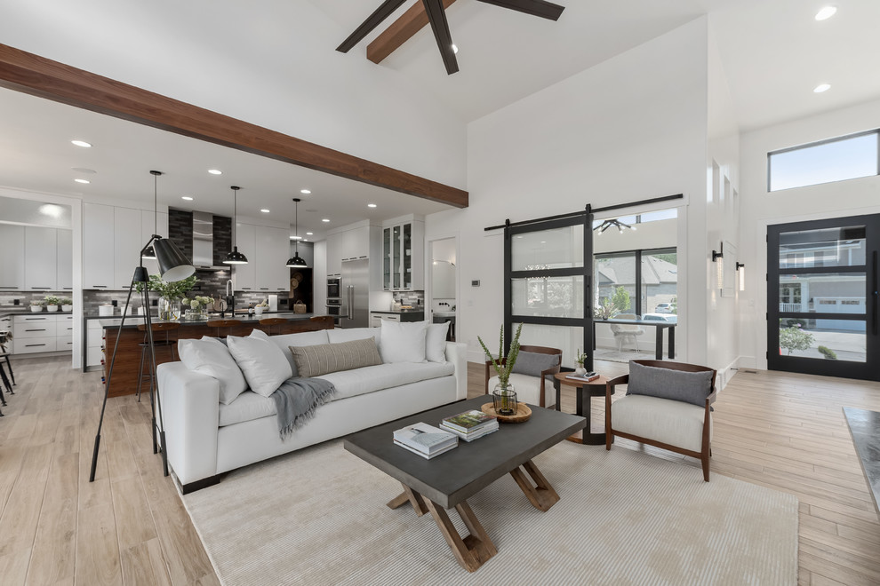 Inspiration for a large contemporary open concept porcelain tile and beige floor family room remodel in Salt Lake City with white walls, a standard fireplace, a tile fireplace and a wall-mounted tv
