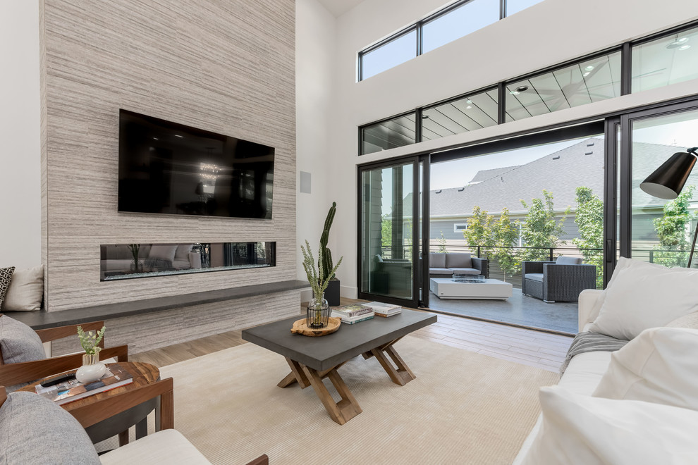 Large trendy open concept porcelain tile and beige floor family room photo in Salt Lake City with white walls, a standard fireplace, a tile fireplace and a wall-mounted tv