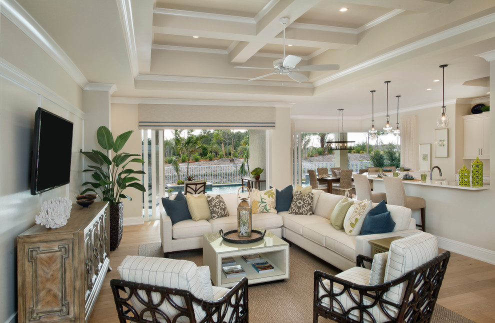 Inspiration for a mid-sized tropical open concept light wood floor and brown floor family room remodel in Miami with beige walls, no fireplace and a wall-mounted tv