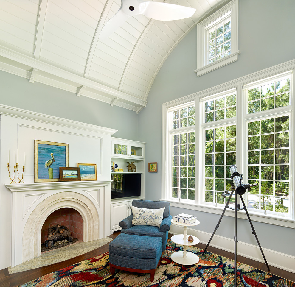Inspiration for a transitional dark wood floor family room remodel in Charleston with blue walls, a standard fireplace and a wall-mounted tv