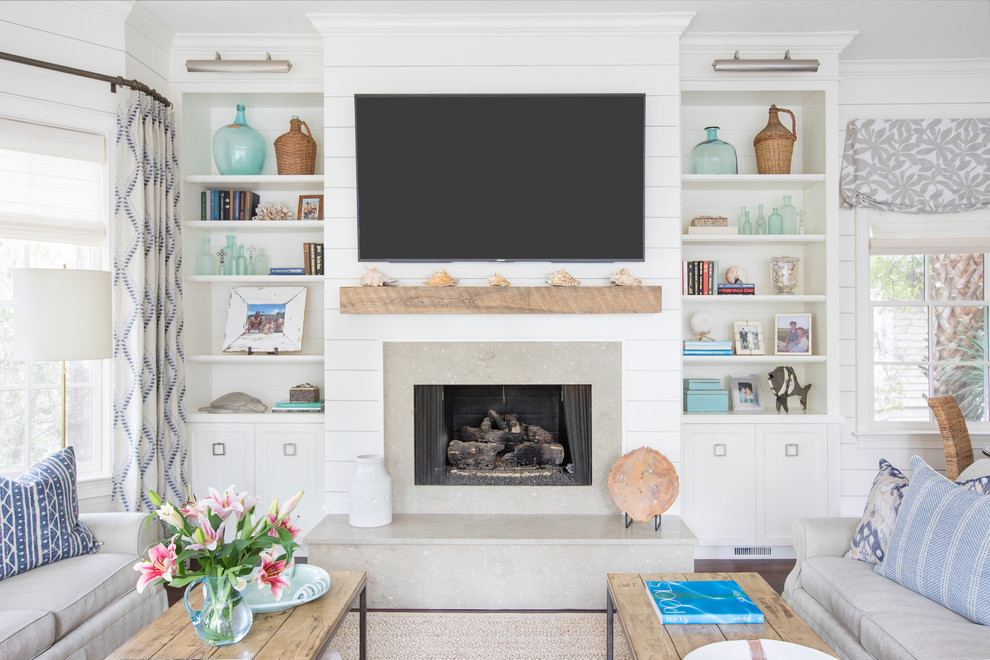 Design ideas for a nautical family and games room in Charleston with white walls, dark hardwood flooring, a standard fireplace, a stone fireplace surround, a wall mounted tv and brown floors.