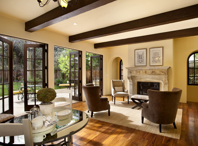 Elegant medium tone wood floor family room photo in San Francisco with beige walls, a standard fireplace and a stone fireplace