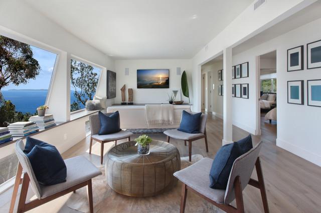 Diseño de sala de estar abierta, clásica renovada, con paredes blancas, suelo de madera oscura y televisor colgado en la pared