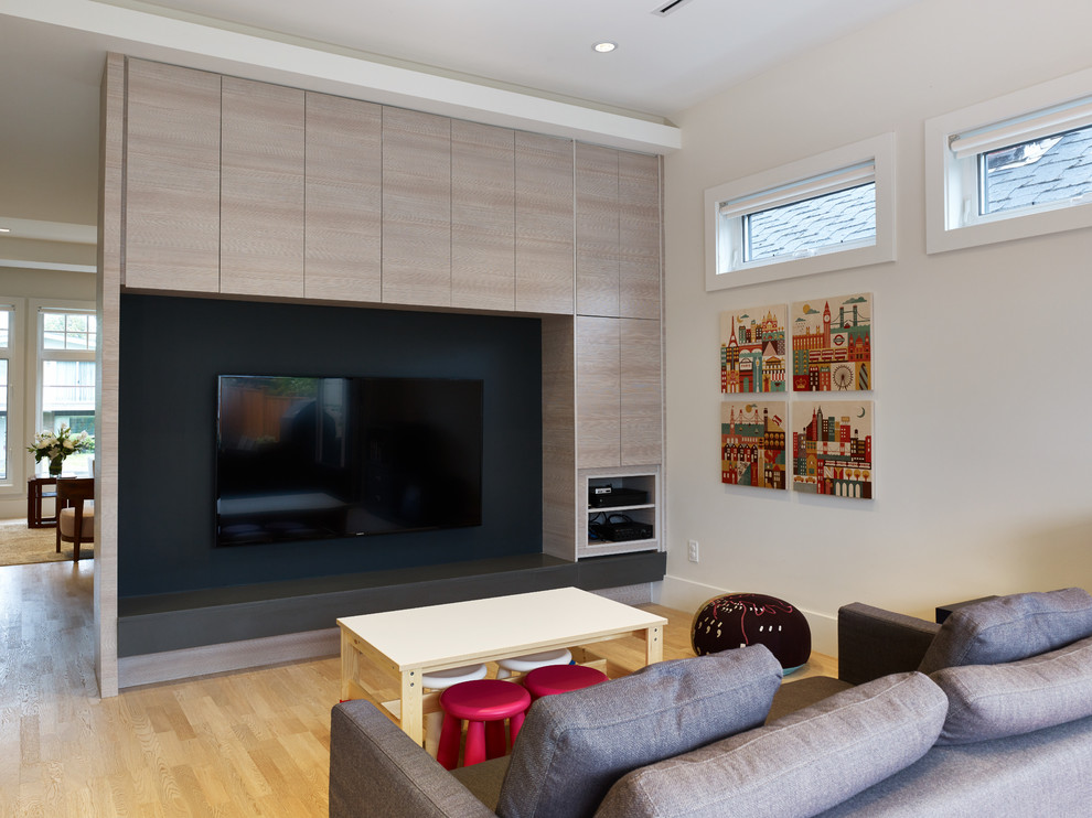 Example of a trendy open concept light wood floor family room design in Vancouver with beige walls, no fireplace and a media wall