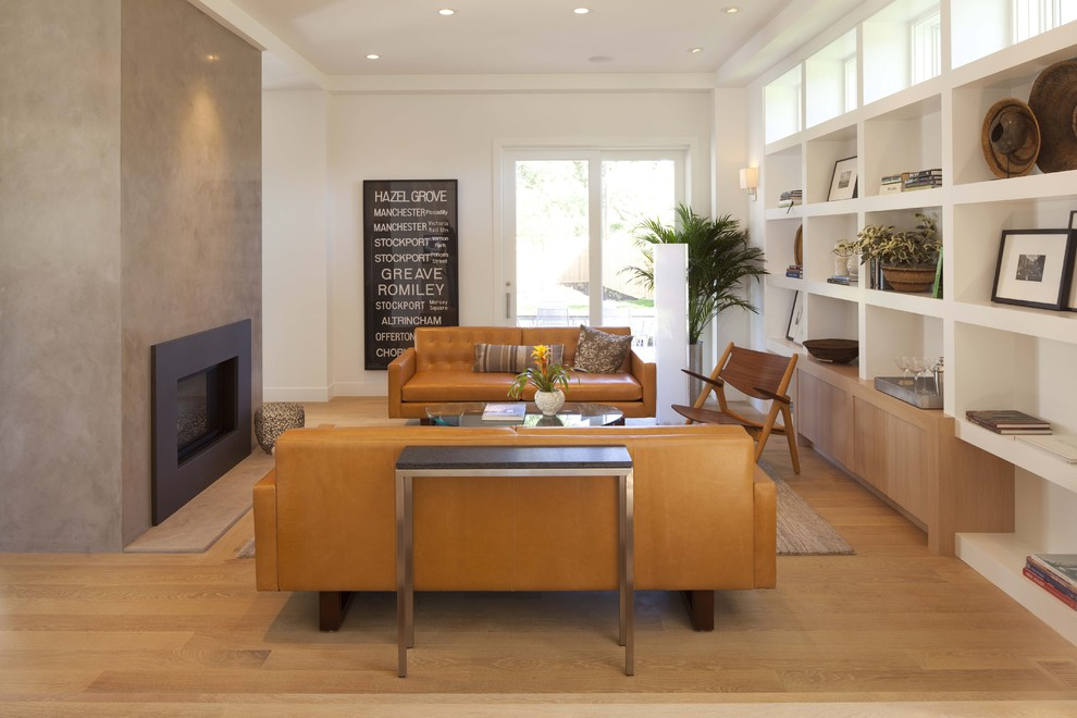 Example of a minimalist medium tone wood floor family room design in Minneapolis with white walls, a standard fireplace and no tv
