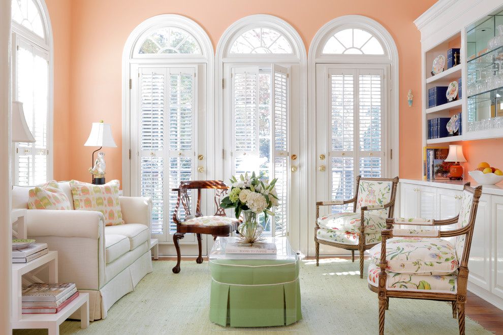 Family room - traditional enclosed medium tone wood floor family room idea in Atlanta with pink walls and no tv