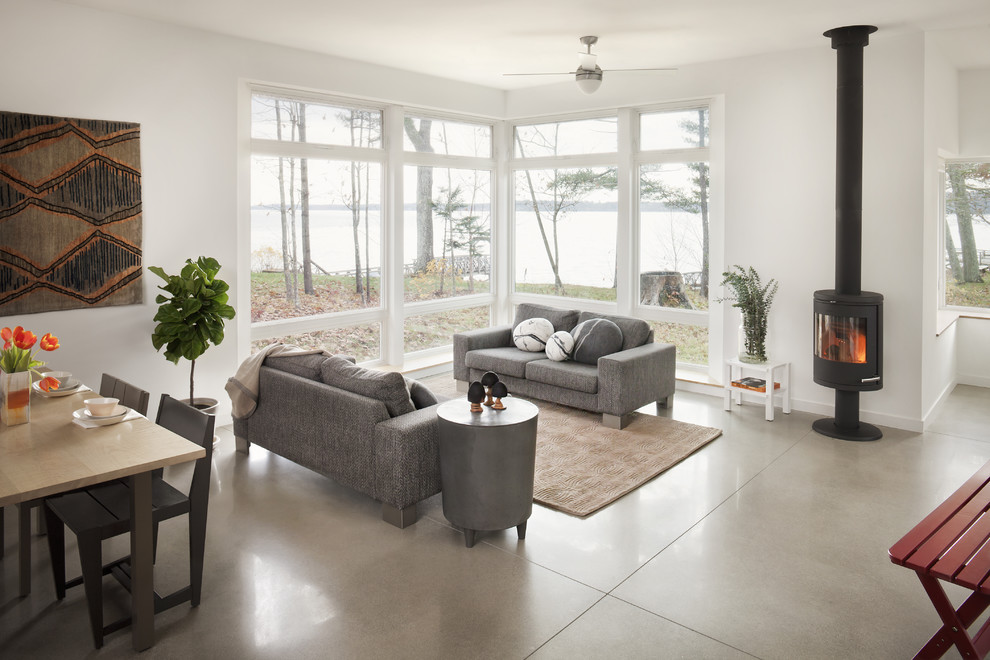 Example of a trendy open concept concrete floor and gray floor family room design in Portland Maine with gray walls and a wood stove