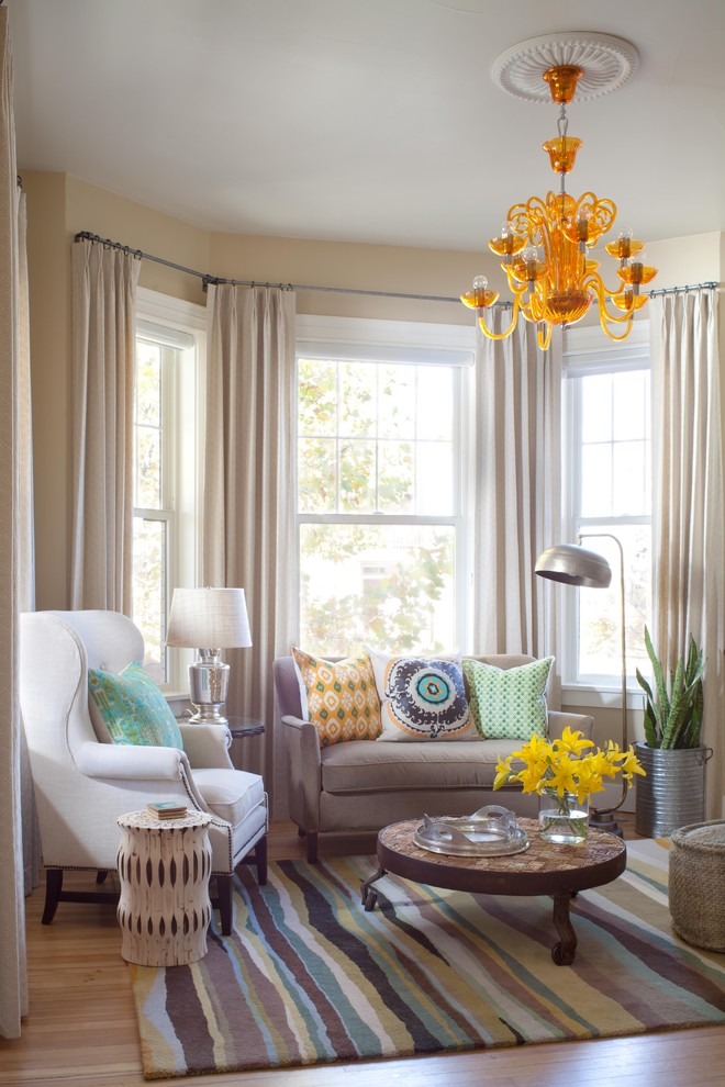 Example of a trendy medium tone wood floor family room design in Denver with beige walls
