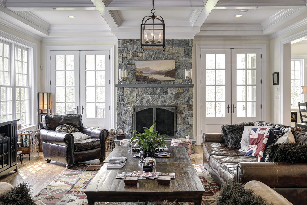 Family room - traditional medium tone wood floor family room idea in DC Metro with beige walls, a standard fireplace and a stone fireplace
