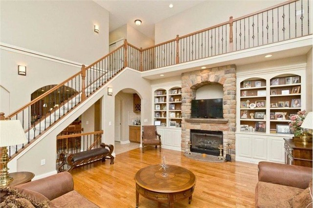Inspiration for a large timeless open concept light wood floor family room remodel in Columbus with beige walls, a standard fireplace, a stone fireplace and a media wall