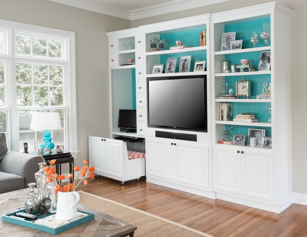 Example of a trendy medium tone wood floor family room design in New York with beige walls and a media wall
