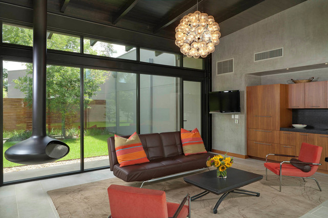 Family room - modern family room idea in Houston with gray walls and a hanging fireplace