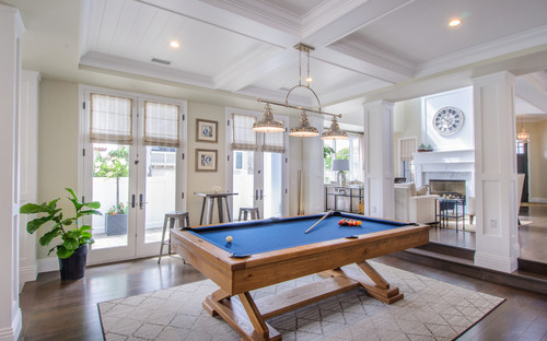 Modern game room with a modern billiard table with a metal pub table and two stools