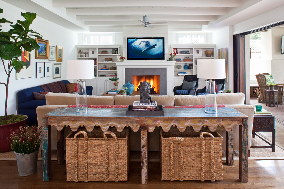 Example of a beach style medium tone wood floor family room design in Los Angeles with white walls, a standard fireplace, a stone fireplace and a wall-mounted tv
