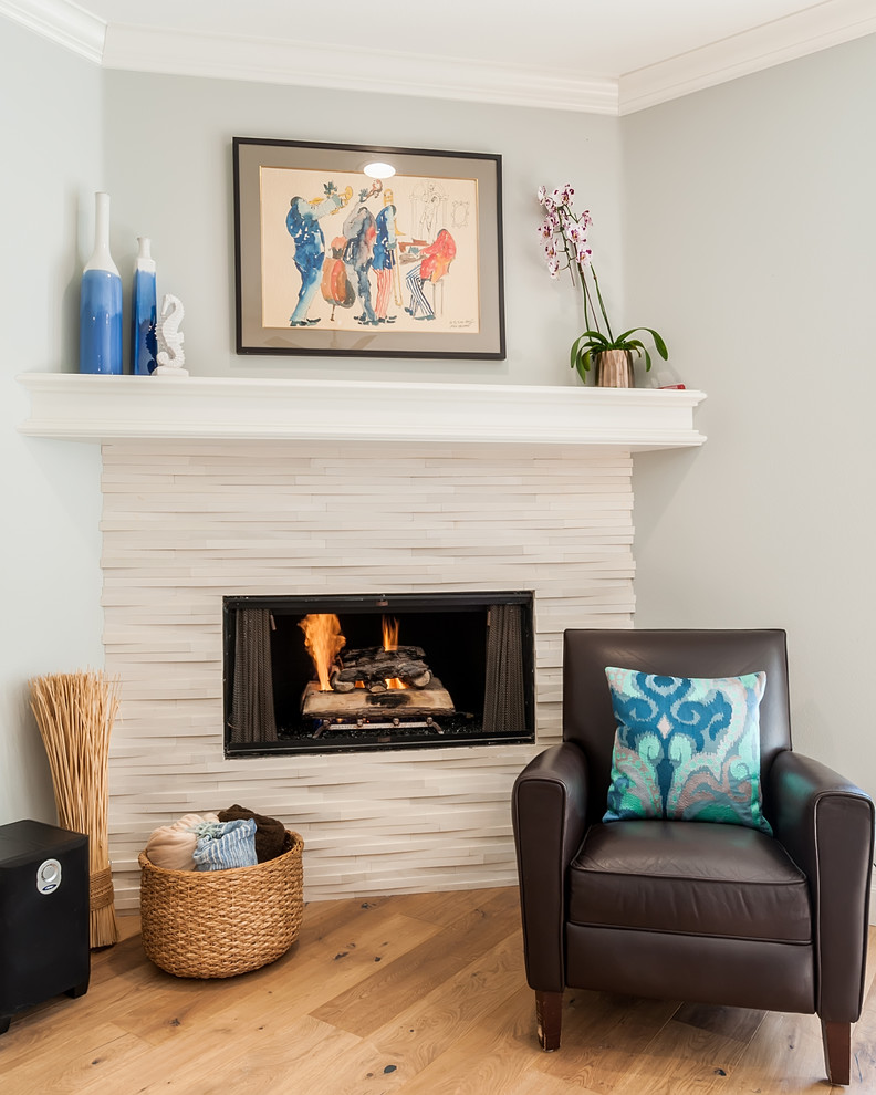 Large beach style open concept light wood floor and multicolored floor family room photo in Los Angeles with gray walls, a corner fireplace, a stone fireplace and a wall-mounted tv