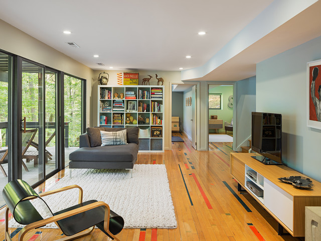 This is an example of a contemporary family and games room in Philadelphia with a freestanding tv, multi-coloured walls, light hardwood flooring and brown floors.
