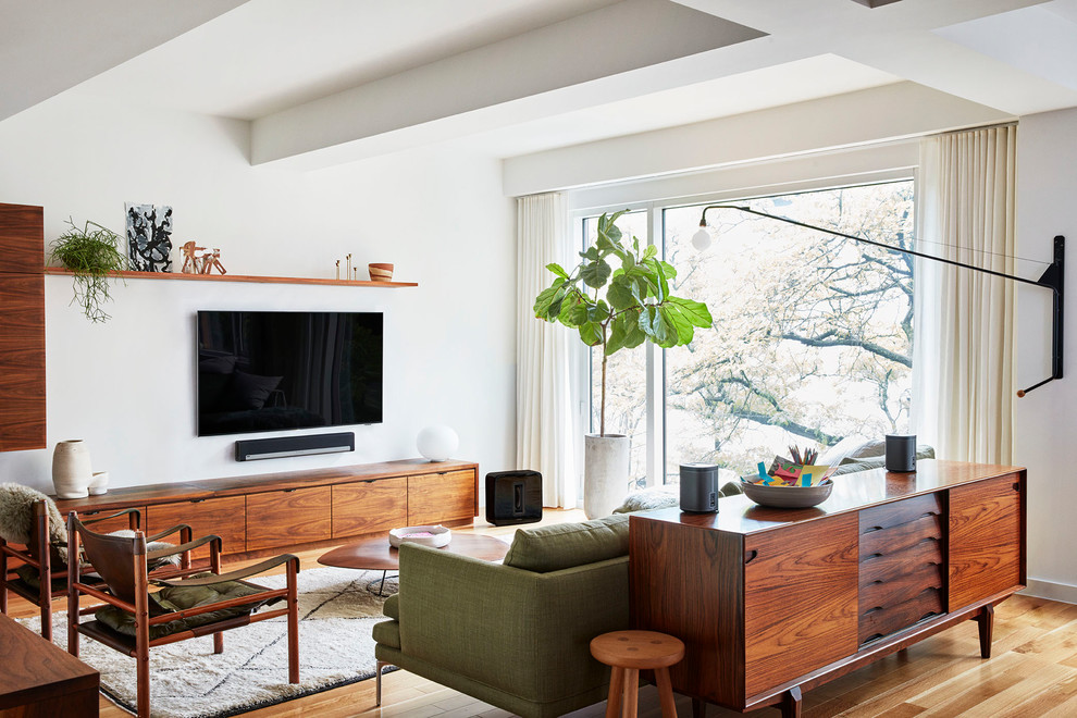 Inspiration for a scandinavian open concept medium tone wood floor and beige floor family room remodel in Los Angeles with white walls and a wall-mounted tv