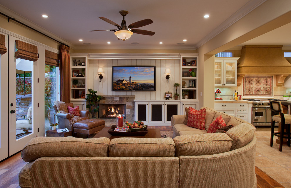 Inspiration for a large timeless open concept medium tone wood floor and brown floor family room remodel in Orange County with beige walls, a standard fireplace, a stone fireplace and a wall-mounted tv