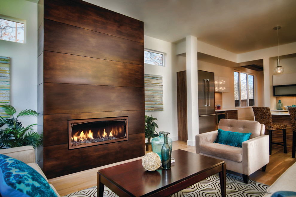 Example of a huge minimalist enclosed light wood floor family room design in Albuquerque with a ribbon fireplace, a metal fireplace, white walls and no tv