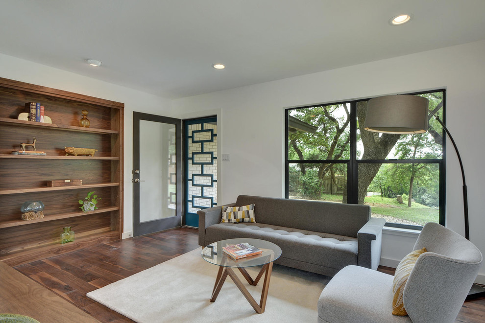 Inspiration for a mid-sized modern enclosed dark wood floor family room library remodel in Austin with no fireplace, a wall-mounted tv and white walls