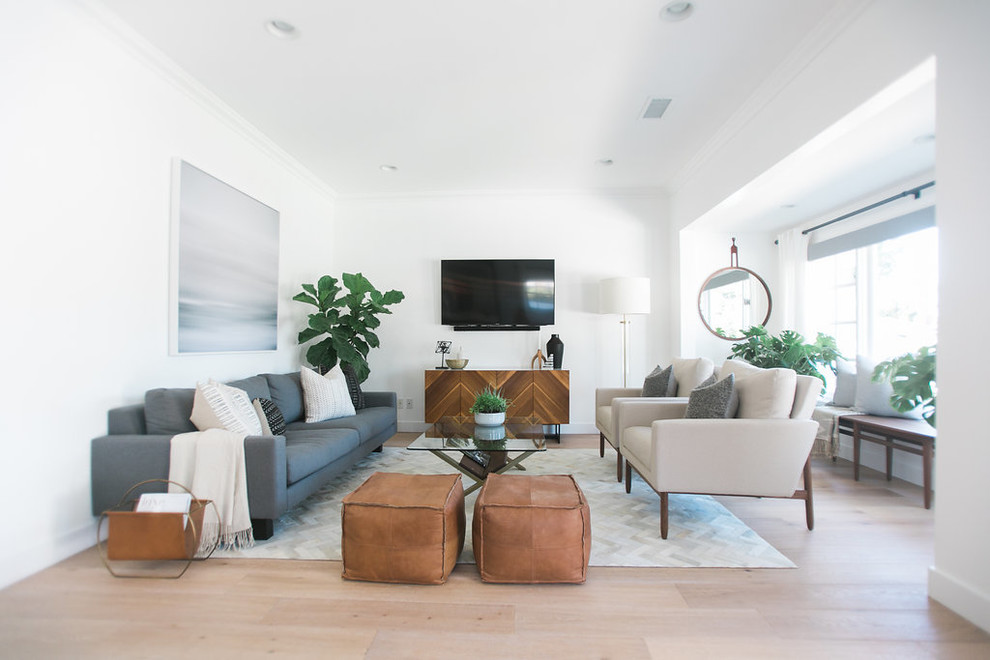 Inspiration for a large midcentury modern open concept light wood floor family room remodel in Orange County with white walls and a wall-mounted tv